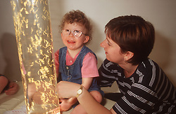 Young girl with visual impairment looking at light column with teacher,