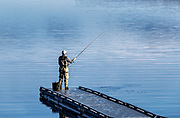 Man flyfishing from a floating dock, Sebago Lake, Standish, Maine, USA.