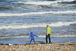 © Licensed to London News Pictures. <br /> 21/10/2014. <br /> <br /> Saltburn, United Kingdom<br /> <br /> A young boy leans into the wind as he visits the beach with family as strong winds continue to lash the coast of Saltburn in England as the tail end of what was Hurricane Gonzalo reached the UK today causing some disruption in parts of the country.<br /> <br /> Photo credit : Ian Forsyth/LNP