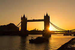 © Licensed to London News Pictures. 03/09/2017. LONDON, UK.  A golden sunrise this morning behind Tower Bridge on the River Thames, as the capital wakes up to a chilly and clear autumn morning. Photo credit: Vickie Flores/LNP