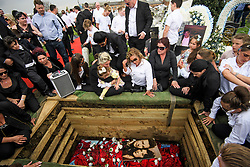 **2018 Pictures of the year by London News Pictures**<br /> © Licensed to London News Pictures. 21/04/2018. London, UK. Mourners gather at the graveside over the coffin at the burial of traveller 'Queenie, Elizabeth Doherty at Kensal Green Cemetery in west London, following a funeral service in Cobham, Surrey. Elizabeth Doherty, whose son Paddy Doherty is known for appearing on My Big Fat Gypsy Wedding and winning Celebrity Big Brother 8, died of a heart attack earlier this month. Paddy Doherty claimed his mother has died of a 'broken heart' following the death of her husband almost a year ago. Photo credit: Ben Cawthra/LNP