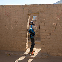 A visitor in a doorway photographing the well-preserved adobe walls of the Incan archaeological site of Tambo Colorado, Pisco, Ica Region, Peru