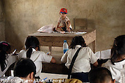 The son of Nang Chanton, a teacher at The Ban Buamlao Primary School in Ban Buamlao, Laos, sits on her desk near the end of the day. Due to the scarcity of day care programs in Laos, Ms. Chanton is accompanied to school by her son each day.