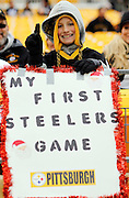 A Pittsburgh Steelers fan signals number one and holds up a sign at his first Steelers game during the NFL week 16 football game against the St. Louis Rams on Saturday, December 24, 2011 in Pittsburgh, Pennsylvania. The Steelers won the game in a 27-0 shutout. ©Paul Anthony Spinelli