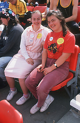 Two young women with disabilities sitting in spectator stand at Special Olympics smiling,