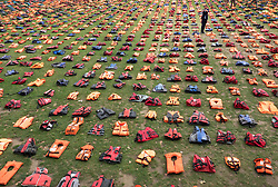 © Licensed to London News Pictures. 19/09/2016. London, UK. A television reporter takes a photograph of a graveyard of life jackets fills Parliament Square ahead of the UN Migration Summit in New York. 2500 of the hi-visibility life jackets abandoned by refugees after crossing from Turkey to the Greek island of Chios have been placed in a grid in the square .  Photo credit: Peter Macdiarmid/LNP