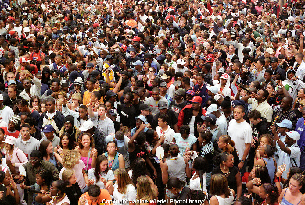 Large multiracial crowd of people  listening to concert in the streets of Notting Hill London.