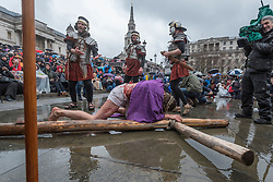"""© Licensed to London News Pictures. 30/03/2018. LONDON, UK.  Jesus, played by James Burke-Dunsmore, falls carrying his cross en route to his crucifixion. The Wintershall Players present their traditional """"The Passion of Jesus"""" play in Trafalgar Square on Good Friday in front of large crowds despite the heavy rain.  The play brings to life the events leading to the crucifixion of Jesus Christ, played by James Burke-Dunsmore, and his subsequent resurrection.  Photo credit: Stephen Chung/LNP"""