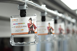 Detail of advertising on passenger hand-strap in carriage on Beijing subway in China