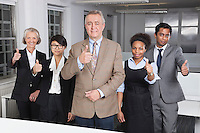 Portrait of multiethnic business group gesturing thumbs up at office