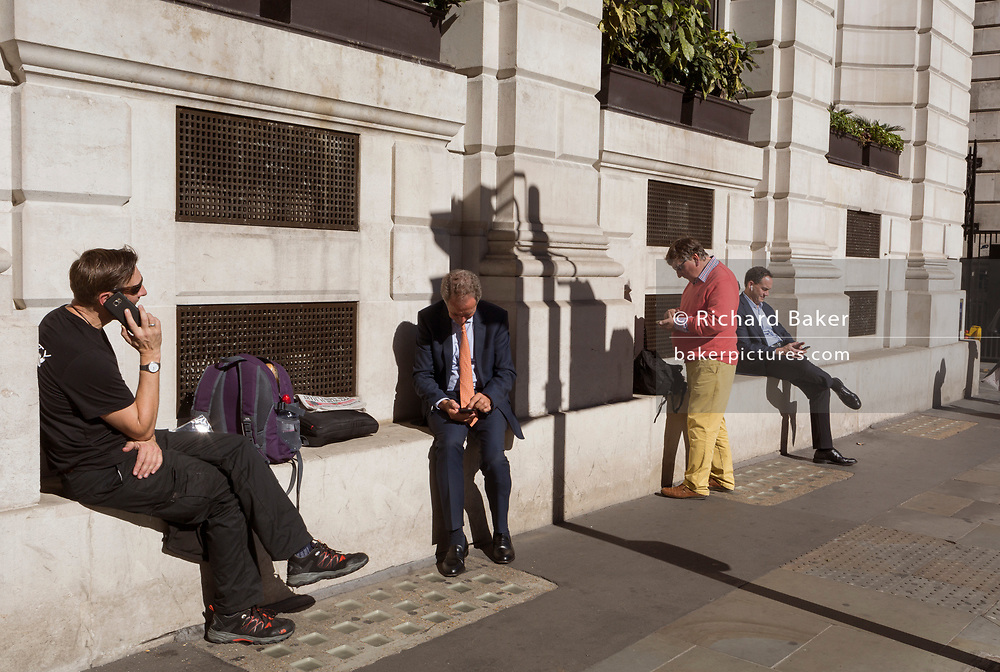 Men check messages and use their phones on Poultry (Street) in the City of London - the capital's financial centre (aka The Square Mile), on 27th September 2018, in London, England.