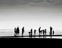 The silhouette of holidaymakers standing on the edge of the tidal paddling pool in Viking Bay, Broadstairs, Kent.