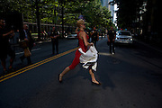 A street performer sprints past a line of law enforcement officers during the 2012 Democratic National Convention on Wednesday, September 5, 2012 in Charlotte, NC.