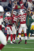Arizona Cardinals strong safety Deone Bucannon (20) and Arizona Cardinals cornerback Jerraud Powers (25) celebrate with Arizona Cardinals free safety Rashad Johnson (26) as Johnson points skyward in celebration after intercepting a third quarter pass at the Green Bay Packers 47 yard line during the NFL NFC Divisional round playoff football game against the Green Bay Packers on Saturday, Jan. 16, 2016 in Glendale, Ariz. The Cardinals won the game in overtime 26-20. (©Paul Anthony Spinelli)