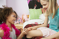 Young girl applying nail polish to friends finger in bedroom