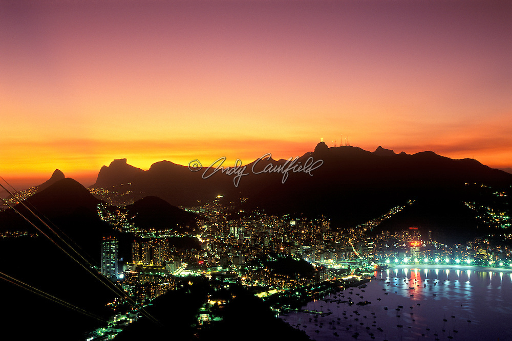 Sunset over Rio de Janeiro as viewed from Sugar Loaf. Corcovado mountain and the illuminated Christ statue is at top center right, Botafogo bay is bottom right, Brazil