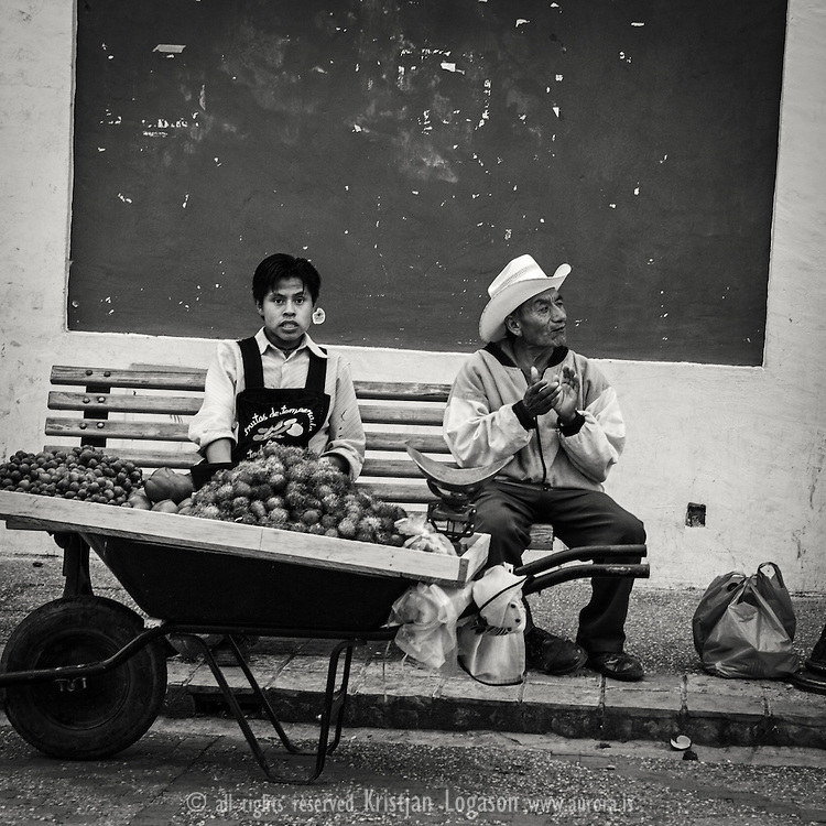 Young fruit vendor and his friend having a good time in one of the walking streets in San Cristobal de las Casas