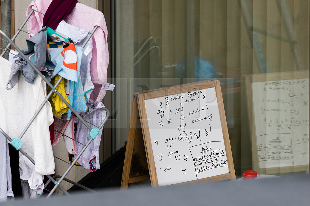 © Licensed to London News Pictures. 04/06/2017. LONDON, UK.  Arabic writing is seen written on a whiteboard through the window of the ground floor flat that is now part of the police cordon at a block of flats in Kings Road, Barking where police arrested several people today in connection with the London Bridge terror attack. Photo credit: Vickie Flores/LNP