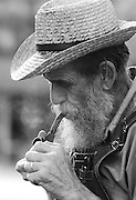 A elderly man lights his pipe.