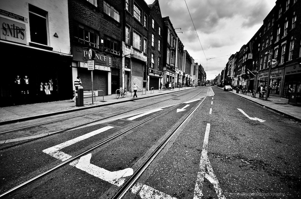 Abbey Street, Dublin City, Ireland on a dark and overcast day. Peeling paint on the tarmac road shows the street markings that guide cars and pedestrians around the Luas tram tracks