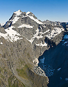 Aerial view of Mount Alba (2360 meters elevation) and the ice filled bowl of Crucible Lake in the Southern Alps, South Island, New Zealand. A terminal moraine dams the cirque which was carved by glaciers. In 1990, UNESCO honored Te Wahipounamu - South West New Zealand as a World Heritage Area.