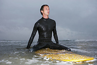 Surfer sitting on surfboard in water