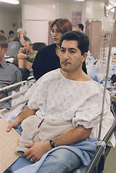 Man with possible kidney complaint waiting with wife in Accident and Emergency department of hospital,