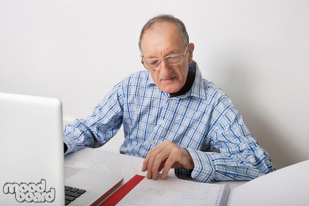 Senior businessman using laptop while reading file at office desk