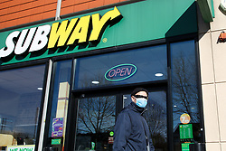 © Licensed to London News Pictures. 23/03/2020. London, UK. A man wearing a face mask walks past Subway in Haringey north London. Subway restaurants across the UK are to close from 7pm tonight as the spread of the coronavirus continues in the country. Photo credit: Dinendra Haria/LNP