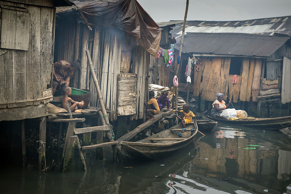 Women and children go about their everyday business from the stilt houses that line the waterways of the Makoko slum.