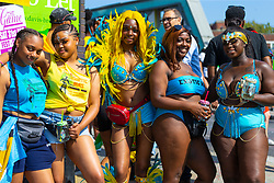 Revellers pose for a picture as day one, Children's Day, of the Notting Hill Carnival gets underway in London. London, August 25 2019.