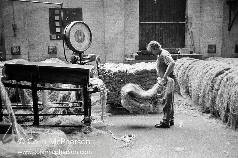 A worker feeding jute into a machine at Tay Spinners mill in Dundee, Scotland. This factory was the last jute spinning mill in Europe when it closed for the final time in 1998. The city of Dundee had been famous throughout history for the three 'Js' - jute, jam and journalism.