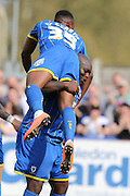 Bayo Akinfenwa forward for AFC Wimbledon (10) bench presses Toyosi Olusanya striker AFC Wimbledon (35) after scoring the penalty to make it 1-0 during the Sky Bet League 2 match between AFC Wimbledon and Newport County at the Cherry Red Records Stadium, Kingston, England on 7 May 2016. Photo by Stuart Butcher.