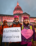 """A man and a woman wearing pink pussy hats smile as they proudly show their signs, """"#Ourmandate #wagelove,"""" and """"Love Trumps Hate!"""" The pink lights of San Francisco City Hall shine behind them moments before the first Women's March San Francisco begins."""