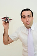 Young Man in his thirties with button down shirt and tie plays with a toy aeroplane