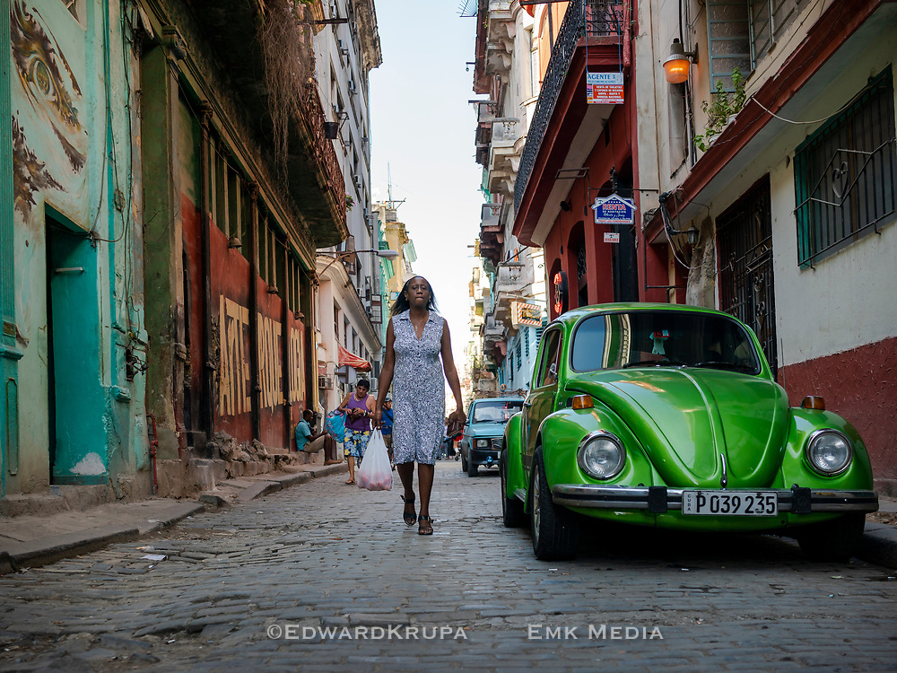 A woman,  in a blue and white dress, walking on a street by a parked green Volkswagen Bug in Old Havana.