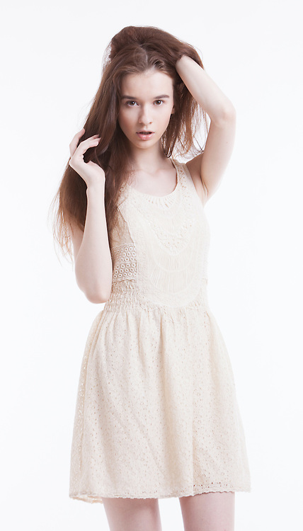Portrait of beautiful young woman in dress with hand in her hair looking away against white background
