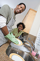 Mid-adult man washing dishes, his girlfriend leaning on kitchen counter, smiling