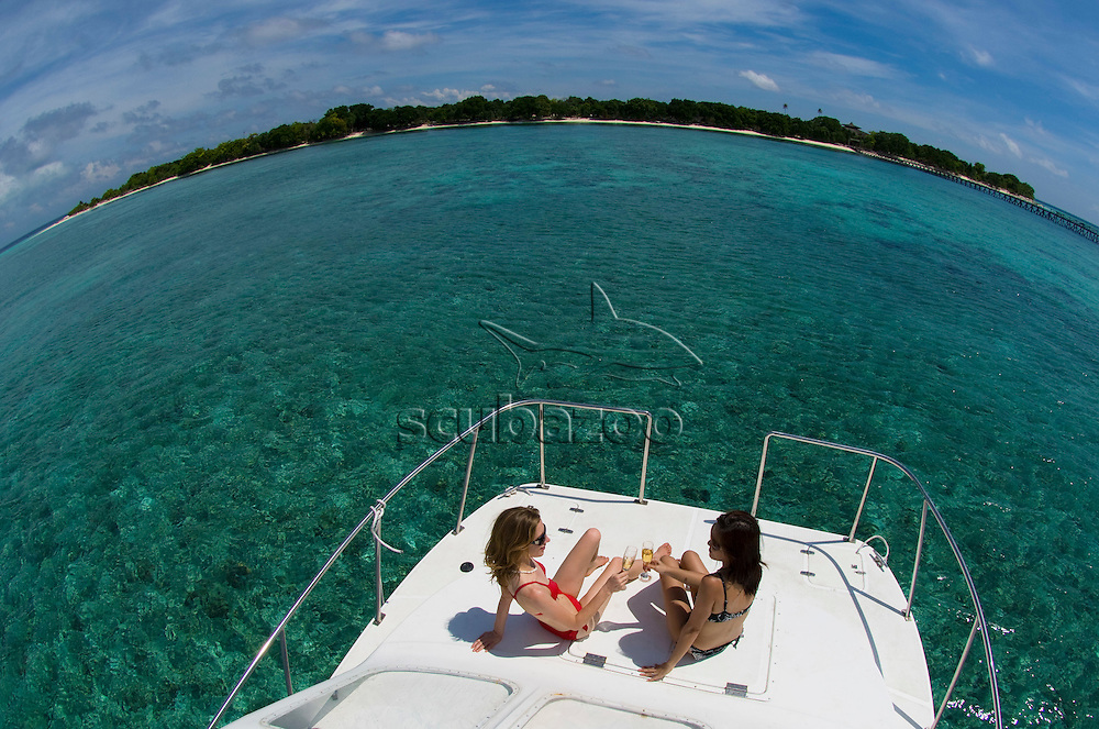 Women relaxing on front of boat, Pom Pom Island Resort, Celebes Sea, Sabah, East Malaysia.