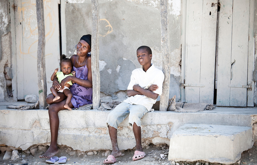 A woman and children rest outside their house in Anse a Galet, Ile de la Gonave, Haiti