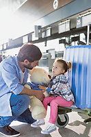 Portrait of man holding teddy bear and playing with his daughter in check in area at airport