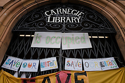 © Licensed to London News Pictures. 01/04/2016. London, UK. Banners hung over the entrace announce the occupation of the Carnegie Library in Herne Hill after local residents refused to leave in an effort to prevent its closure. Lambeth Council had planned to close the library last night (31st March) in order to turn it into a 'healthy living centre'. Photo credit : Rob Pinney/LNP