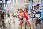 13 APRIL 2014 - BANGKOK, THAILAND: Thais walk through a water fight on Khao San Road in Bangkok. Songkran is celebrated in Thailand as the traditional New Year's Day from 13 to 16 April. Songkran is in the hottest time of the year in Thailand, at the end of the dry season and provides an excuse for people to cool off in friendly water fights that take place throughout the country. Songkran has been a national holiday since 1940, when Thailand moved the first day of the year to January 1.    PHOTO BY JACK KURTZ