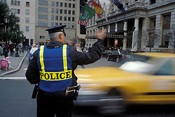 Police officer directing traffic near Plaza Hotel and Central Park entrance, NYC