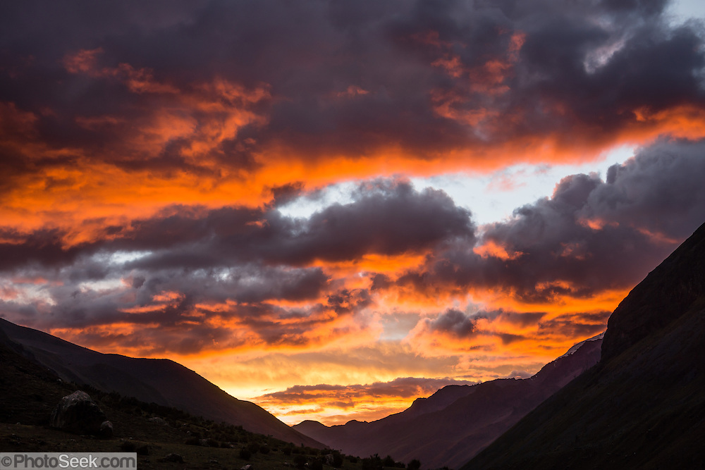 Sunset turns clouds orange and yellow over Alpamayo Valley, Cordillera Blanca, Andes Mountains, Peru, South America. Day 6 of 10 days trekking around Alpamayo in Huascaran National Park (UNESCO World Heritage Site).