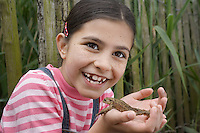 Girl (5-6) holding toad by reeds