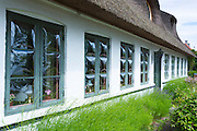 Convex glass windows of thatched cottage at Trofense off Svendborg, part of South Funen Archipelago, Denmark