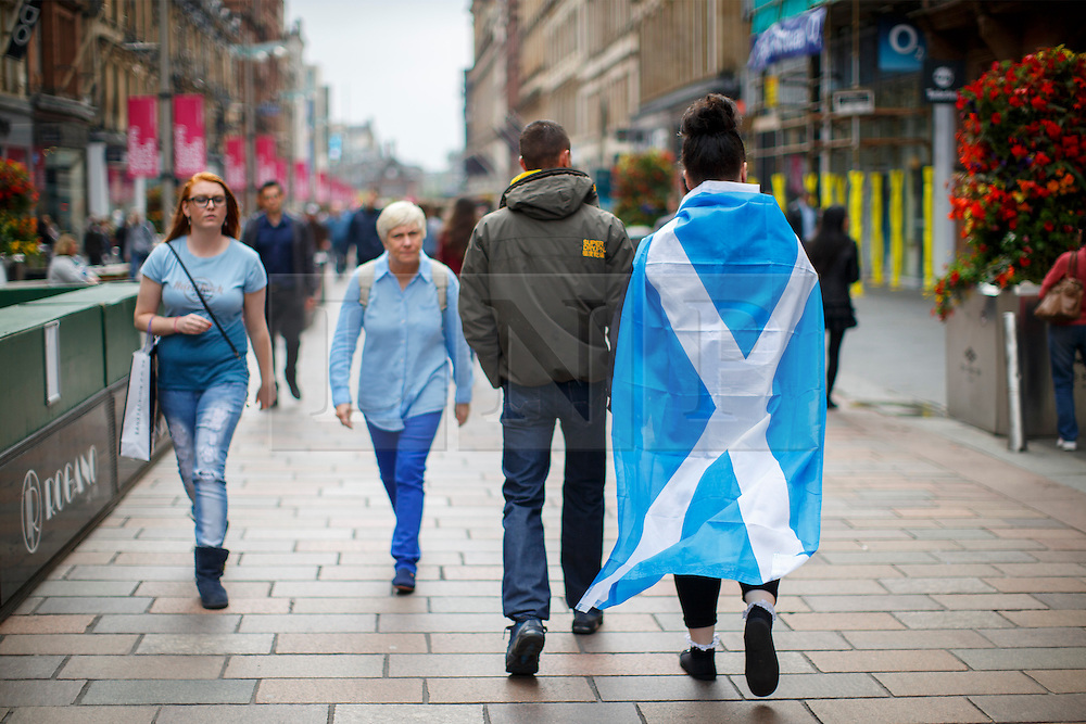 © Licensed to London News Pictures. 18/09/2014. Glasgow, UK. A woman with Scottish Saltire flag walking in Glasgow city centre whilst people of Scotland going to polling stations to vote on the Scottish independence referendum on Thursday, 18 September 2014. Photo credit : Tolga Akmen/LNP