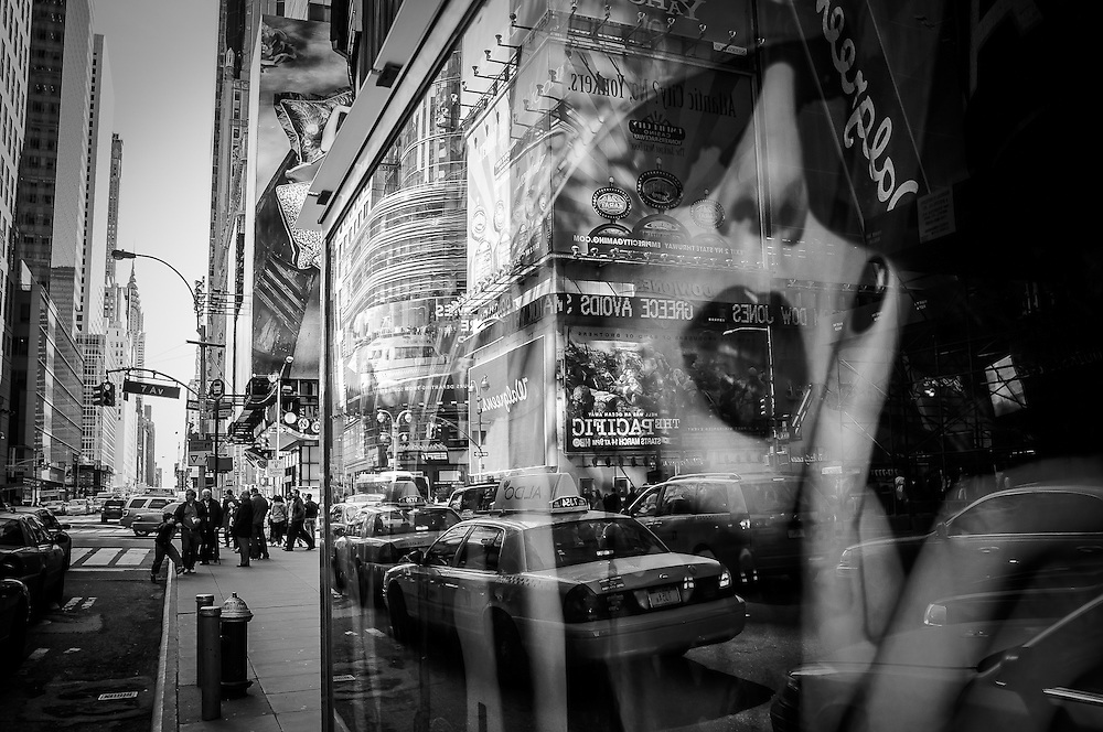 The streets of Times square are being reflected in the back of a news stand, with the Chrysler Building in the background, Manhattan, New York, 2010.