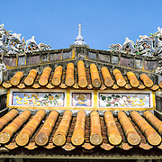The ornate roof of a restored pagoda at the Imperial City in Hue, Vietnam. A self-enclosed and fortified palace, the complex includes the Purple Forbidden City, which was the inner sanctum of the imperial household, as well as temples, courtyards, gardens, and other buildings. Much of the Imperial City was damaged or destroyed during the Vietnam War. It is now designated as a UNESCO World Heritage site.